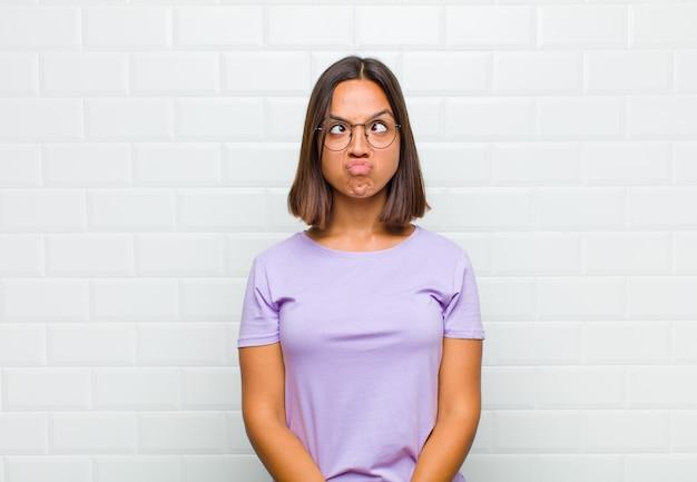 Латинская женщина выглядит глупо и смешно с глупым косоглазым выражением лица, шутит и дурачит