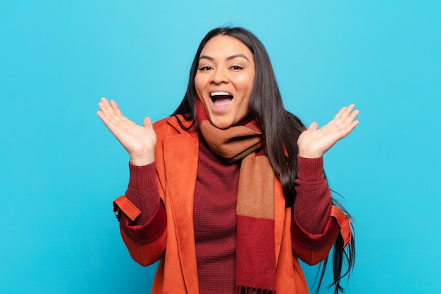 Latin woman looking happy and excited, shocked with an unexpected surprise with both hands open next to face