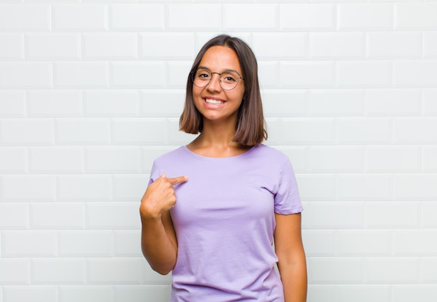 Latin woman looking proud, confident and happy, smiling and pointing to self or making number one sign