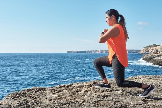 ラテン女性、中年、スポーツウェアの着用、トレーニング、運動、板、腹筋運動、登山者のステップ、カロリーの燃焼、健康維持、海沿いの屋外、ヘッドフォンの着用、スマートウォッチ