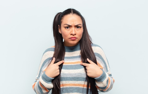 Latin woman pointing to self with a confused and quizzical look, shocked and surprised to be chosen
