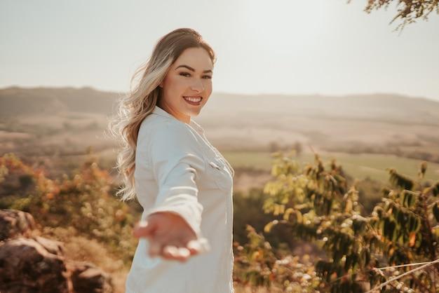 ラテン系の女性がカメラに手を伸ばし、旅行に招待します。私と来て。
