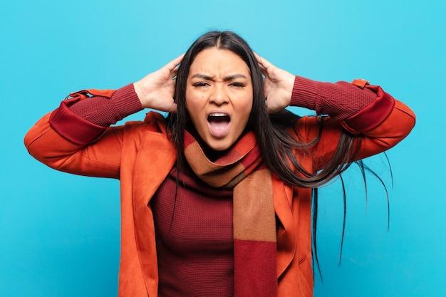 Латинская женщина кричит в панике или гневе, шокирована, напугана или разъярена, с руками у головы