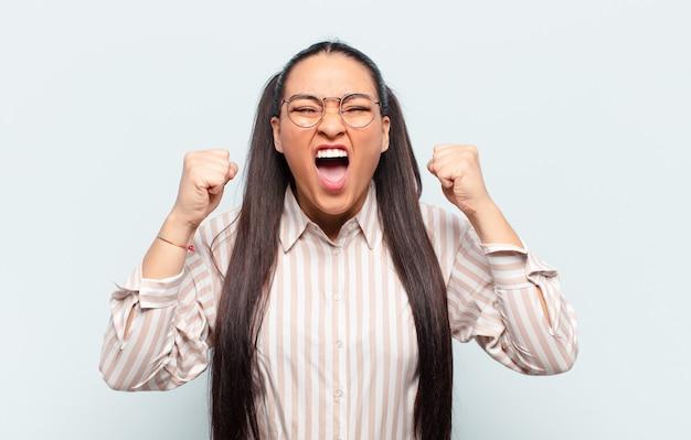 怒りの表情や成功を祝う拳を握り締めて積極的に叫ぶラテン女性