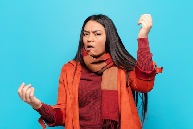멍청하고, 미친, 혼란스럽고, 당황한 표정으로 어깨를 으쓱하는 라틴 여자