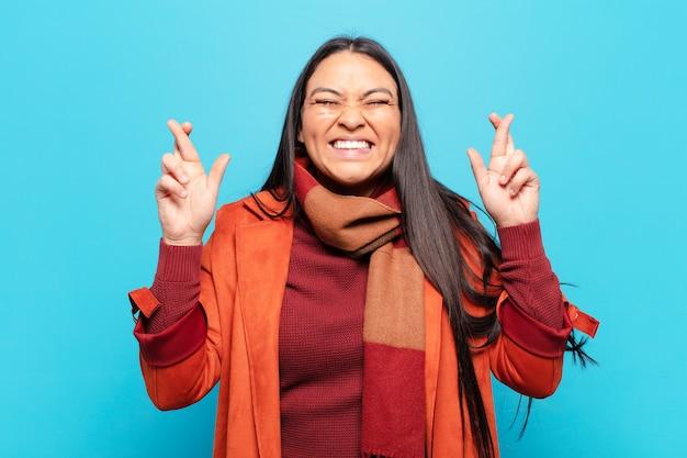 Латинская женщина улыбается и тревожно скрещивает пальцы, чувствуя беспокойство и желая или надеясь на удачу
