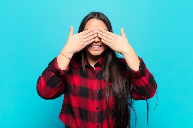 Латинская женщина улыбается и чувствует себя счастливой, прикрывая глаза обеими руками и ожидая невероятного сюрприза