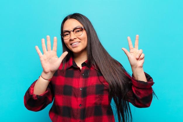 라틴 여자 웃고 친절하게보고, 앞으로 손으로 8 또는 8 번째를 보여주는, 카운트 다운