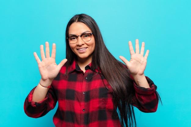 Латинская женщина улыбается и выглядит дружелюбно, показывает десятый или десятый номер рукой вперед, отсчитывает