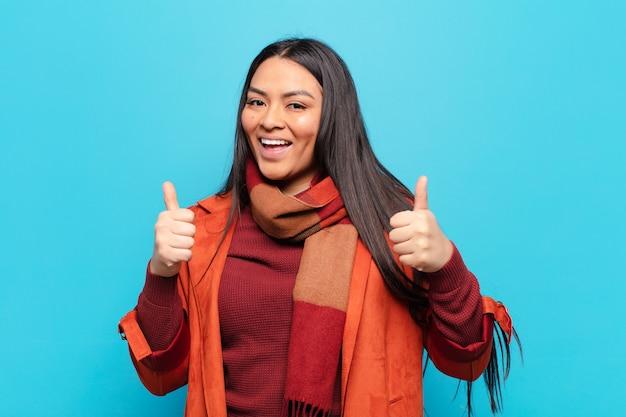 두 엄지 손가락으로 광범위하게 행복하고 긍정적이며 자신감 있고 성공적인 모습을 보여주는 라틴 여자