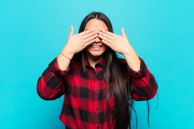 Latin woman smiling and feeling happy, covering eyes with both hands and waiting for unbelievable surprise