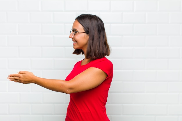 笑顔、挨拶、握手を提供して成功した取引、協力の概念を閉じるラテン女性