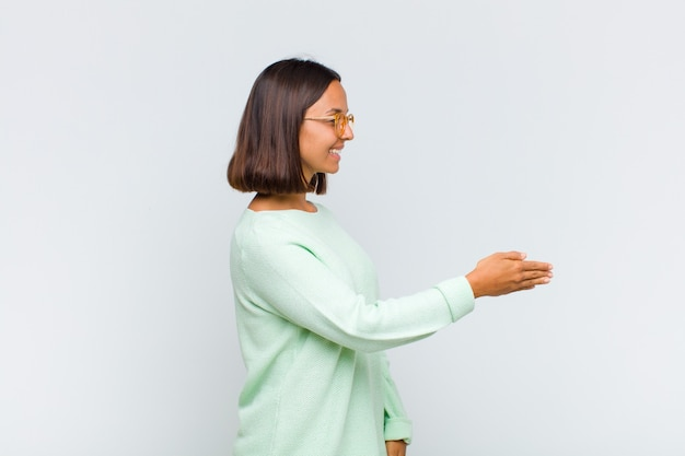 Latin woman smiling, greeting you and offering a hand shake to close a successful deal, cooperation concept
