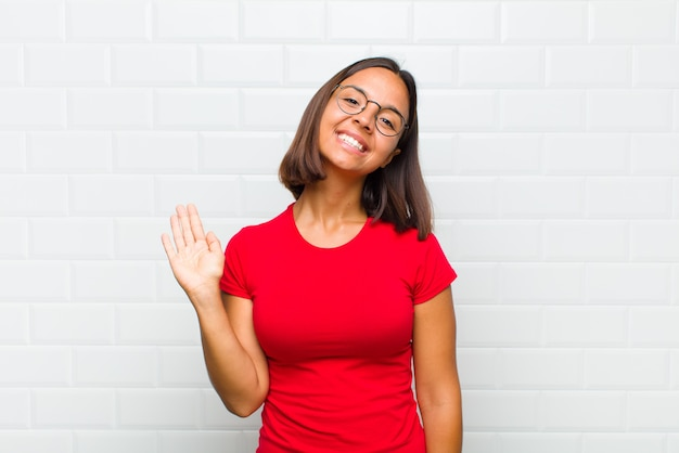 Latin woman smiling happily and cheerfully, waving hand, welcoming and greeting you, or saying goodbye