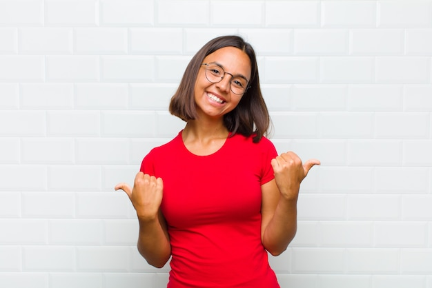 Latin woman smiling joyfully and looking happy, feeling carefree and positive with both thumbs up