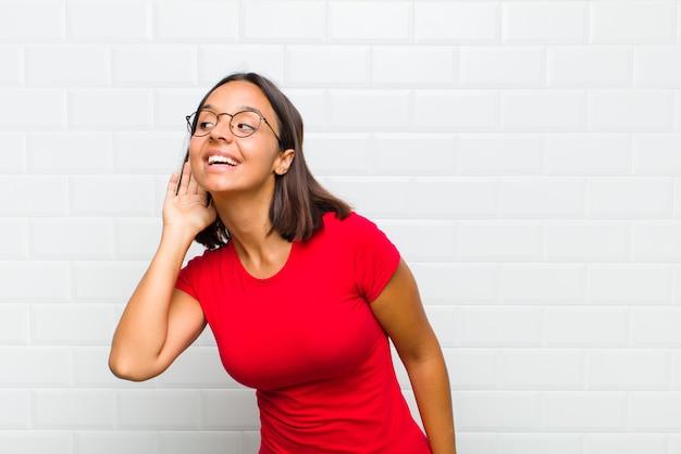 Латинская женщина улыбается, с любопытством смотрит в сторону, пытается слушать сплетни или подслушивает секрет