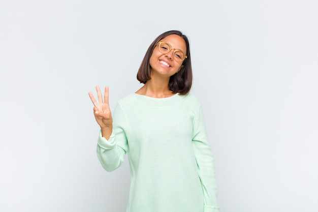Latin woman smiling and looking friendly, showing number one or first with hand forward, counting down