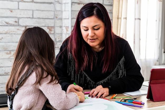 Латинская женщина учится со своей дочерью дома
