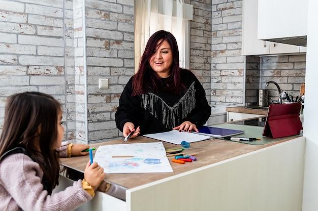 自宅で娘と一緒に勉強しているラテン女性