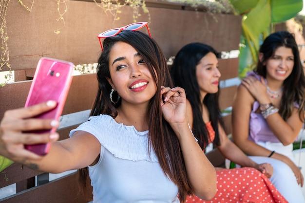 友達とセルフィーを撮るラテン系女性素敵な笑顔のヒスパニック系の女の子が写真を撮る