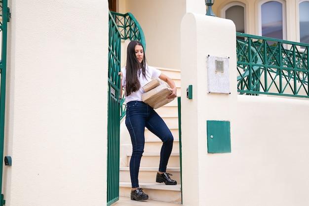 ラテン系の女性が注文を取り、外部ゲートを閉じます。思いやりのある若い女性客が自宅で急行注文を受け、段ボール箱を持っています。配送サービスとオンラインショッピングのコンセプト