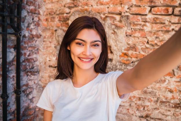 Latin woman taking a selfie.