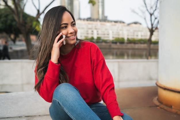 電話で話しているラテン系の女性。