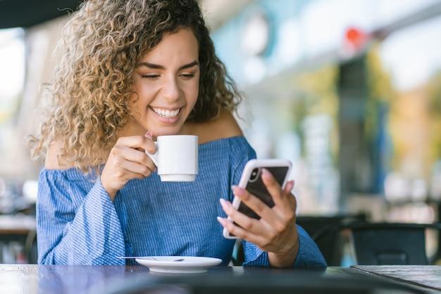 コーヒーショップでコーヒーを飲みながら携帯電話を使用しているラテン女性。アーバンコンセプト。