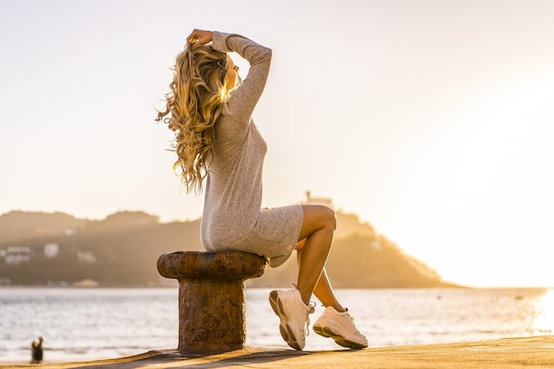 夕暮れ時の海岸の海のそばに座っているブロンドの髪のラテン女性