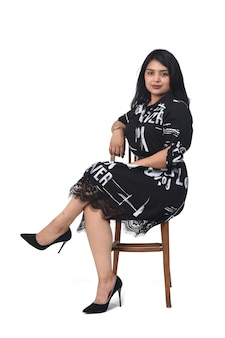 Latin woman with dress and high heels sitting on chair