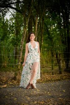 緑の夏のドレスのモデリングと森の真ん中で笑顔のラテン女性。