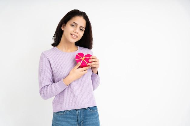 흰색 바탕에 손에 심장 모양의 선물 상자와 라틴 여자
