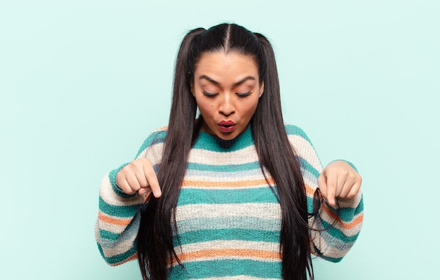 Latin woman with open mouth pointing downwards with both hands, looking shocked, amazed and surprised