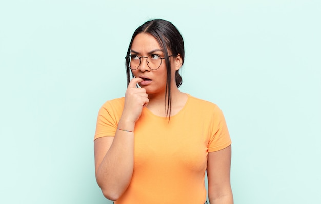 놀란, 긴장, 걱정 또는 겁 먹은 표정으로 라틴 여자, 복사 공간을 향해 측면을 찾고