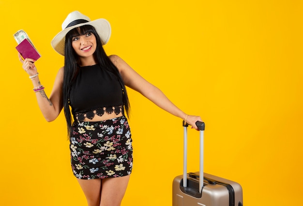 Latin woman with travel suitcase yellow space