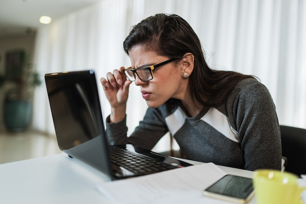 노트북에서 온라인 콘텐츠를 읽으려는 시력 문제가 있는 라틴 여성