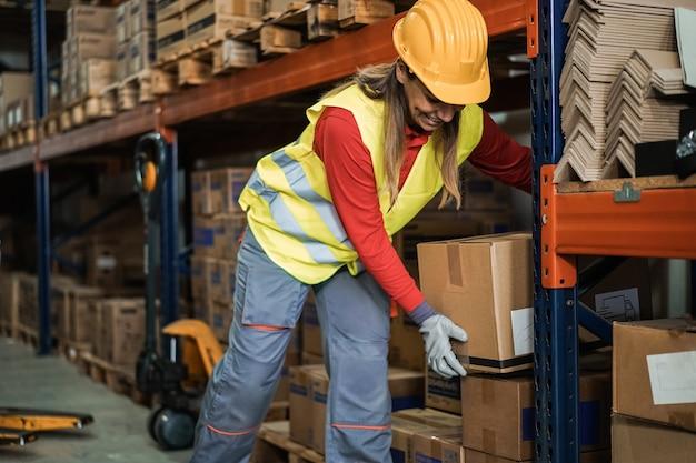 Латинская женщина-работник загружает коробки для доставки внутри склада - основное внимание уделяется картонной упаковке