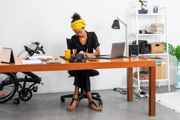 ノートパソコンとドキュメントでホームオフィスで働くラテン女性