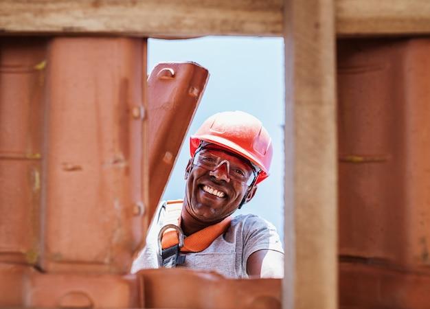 Латинский рабочий устанавливает желтую керамическую черепицу на деревянные доски
