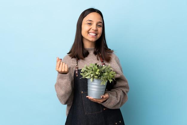 青い壁の上のラテンの若い庭師女性
