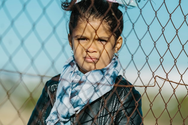 Latin young girl looking at the camera with an serious and angry expression, behind a fence, in a blue sky background. childhood and education concept.