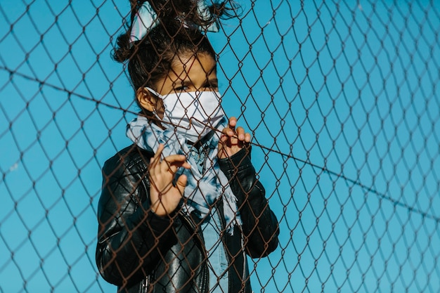 Latin young girl wearing a mask, looking at the camera with an serious expression, behind a fence, in a blue sky background. she has her hands on the fence. childhood and coronavirus concept.