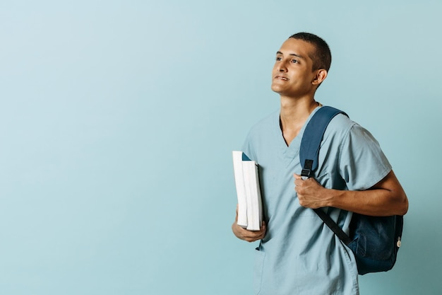 의료복을 입은 라틴 청년은 책과 배낭을 들고 있습니다. 교육 개념입니다.