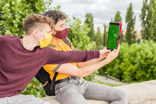 라틴 젊은이는 새로운 일반 전염병 크로마 키 터치스크린에서 디지털 태블릿 사회적 거리를 사용합니다.