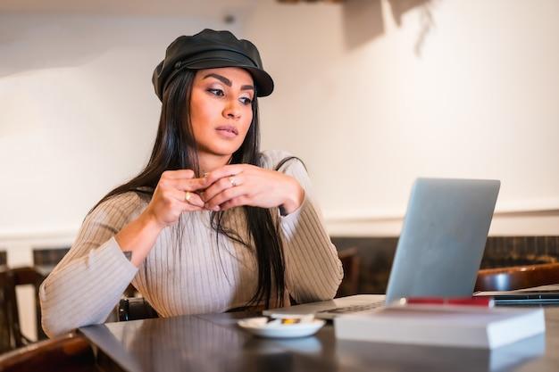 휴가 중 카페테리아에서 컴퓨터 재택 근무로 업무 이메일을 읽는 라틴계 갈색 머리 건축가