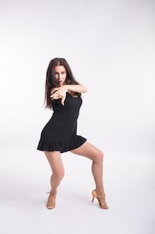 Концепция танца латиноамериканца, стрип-танца, современника и bachata - женщина импровизирует танцевать и двигает ее длинные волосы на белую предпосылку.