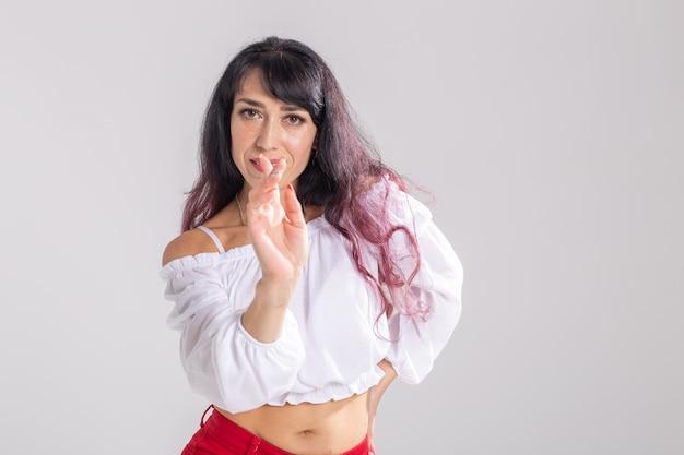 라티나 댄스, 스트립 댄스, 현대 및 바차타 여성 개념 - 여성이 즉흥적으로 춤을 추고 흰색 배경에서 긴 머리를 움직입니다.