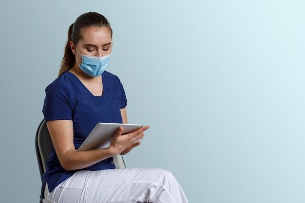 Латинская медсестра с маской сидит, работая с цифровым планшетом