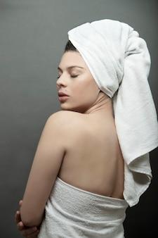 中立的な背景の頭に白いタオルでプロファイルのラティーナ女性