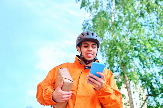 Latino bicycle deliveryman using his smart phone to deliver a package